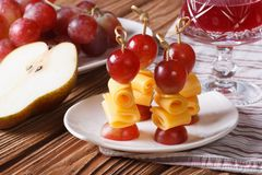 Red grapes and cheese on skewers and a glass of wine close-up Stock Image