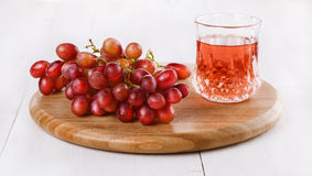 Red grapes on chopping board with glass of spritzy drink. Red grapes on a round chopping board with glass of spritzy drink on a white wooden background royalty free stock image