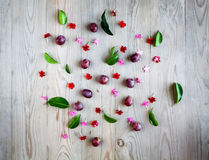 Red grapes with flowers on wooden board Stock Photos