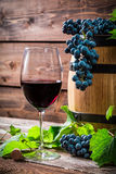 Red grapes and a glass of red wine. On old wooden table Stock Image