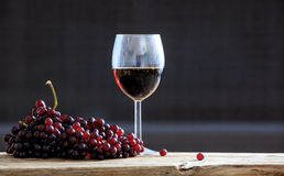 Red grapes and a glass of wine. On a wooden table Stock Photography