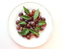 Red grapes with green leaves. Fresh red grapes with green leaves on white background Stock Photography