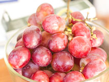 Red grapes have white stains in the glass bowl. Stock Image