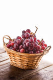Red grapes in knitted basket. On wooden old rustic table and white background Stock Photo
