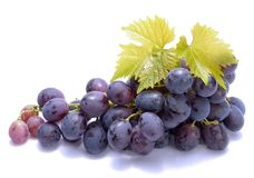 Red grapes with leaves on white background Royalty Free Stock Photos