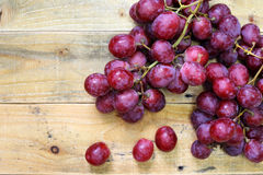 Red grapes on old wood table Royalty Free Stock Image