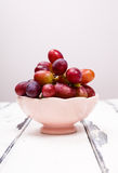 Red Grapes in pink bowl on white vintage table. Red Grapes in pink bowl front view stock photo