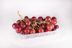 Red grapes in plastic container isolated on white background. Fresh red grapes Stock Image