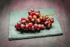 Red grapes on stone. Red grapes on gray stone Stock Photo