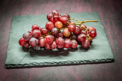 Red grapes on stone. Red grapes on gray stone Royalty Free Stock Images