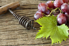 Red grapes with vine leaves. Old corkscrew with wooden handle lies between red grapes and vine leaves on rustic wooden background Stock Images
