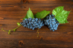 Red grapes with a vine. On a wooden background Stock Photos