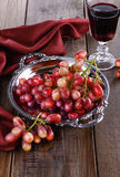 Red grapes on a vintage tray with glass of wine. Red grapes on a vintage metal tray with glass of wine on rustic wooden background stock image
