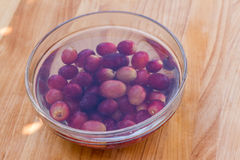 Red grapes in water served in glass bowl on wooden cutting board Royalty Free Stock Photography
