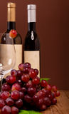 Red grapes with wine bottles Royalty Free Stock Photography