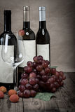 Red grapes with wine bottles Stock Images