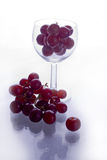 Red grapes in wine glass. Red grapes inside a wine glass Stock Image