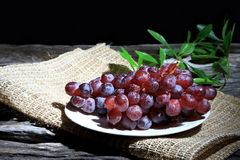 Red grapes on wooden board background. Red grapes on wooden board background, Dark tone Royalty Free Stock Image