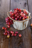 Red grapes in a wooden bucket on wooden background Royalty Free Stock Image