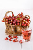 Red grapes in a woven basket with glass of juice. On a white wooden background royalty free stock images