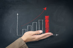 Red graph. Red arrow graph on hand blackboard Stock Images