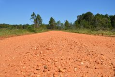 A red gravel road with no people in Alabama, USA. A generic red gravel road with no people under a bright blue sky in Alabama, USA royalty free stock photography