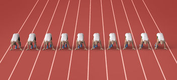 Red gravel running track with athletes in start position.  Royalty Free Stock Image