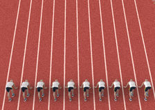 Red gravel running track with athletes in start position.  Stock Image