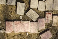 Red and gray bricks lie on yellow earth. view from above. rough surface texture. A red and gray bricks lie on yellow earth. view from above. rough surface stock image