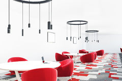 Red and gray cafe interior. Cafe interior with a gray and red carpet, red armchairs standing near round tables and original ceiling lamps. Posters on the walls Stock Images