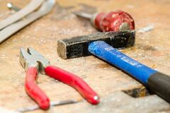 Red and Gray Pliers Beside Blue and Black Hammer Stock Image