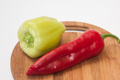 Red and greeen paprikas on the kitchen wooden cutting board.  Stock Photography