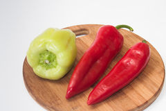 Red and greeen paprikas on the kitchen wooden cutting board.  Stock Photo