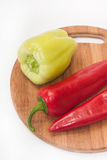 Red and greeen paprikas on the kitchen wooden cutting board.  Royalty Free Stock Image