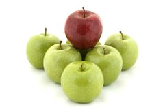 Red on Green. A red apple sits on top of six green apples Royalty Free Stock Photo