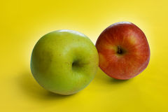 Red and green apple. On a yellow background Royalty Free Stock Photos