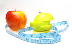 Red and green apple healthy eating. Single red apple with a green apple sliced up plus blue tape measure Royalty Free Stock Photo