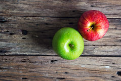 Red and green apple on old wooden table Stock Photos