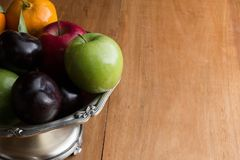 Heap colourful fruit in the silver bowl on the rustic wood table background. Red and green apple plums and tangerine in the silver bowl on the wood table royalty free stock photos