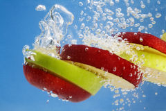 Red and Green apple slices underwater Royalty Free Stock Image