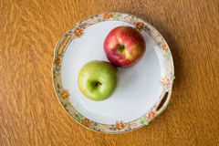 Red and green apples on an antique plate. Two apples on an antique plate over wooden background Stock Image