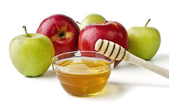 Red and green apples and a bowl of honey Stock Image