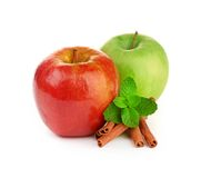 Red and green apples, cinnamon sticks and mint Stock Photos