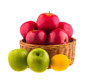Red and green apples, and lemon in a wooden basket. Royalty Free Stock Images