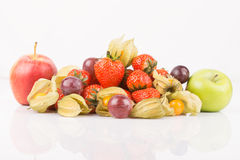 Red and green apples with orange physalis, purple grapes and red strawberries. Royalty Free Stock Images