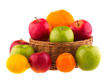 Red and green apples, oranges and lemons in a wooden basket Stock Image