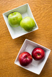 Red and green apples in square bowls. Four apples in bowls provide a healthy snack with choices among green and red varieties Stock Image