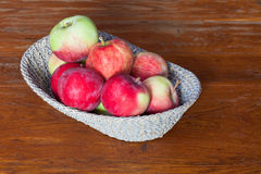 Red and green apples in straw basket Royalty Free Stock Images