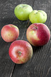 Red and green apples on a table. Red and green apples on the  wooden table Stock Image