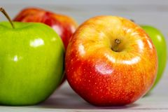 Red and green apples waiting to be eaten on the kitchen table stock images